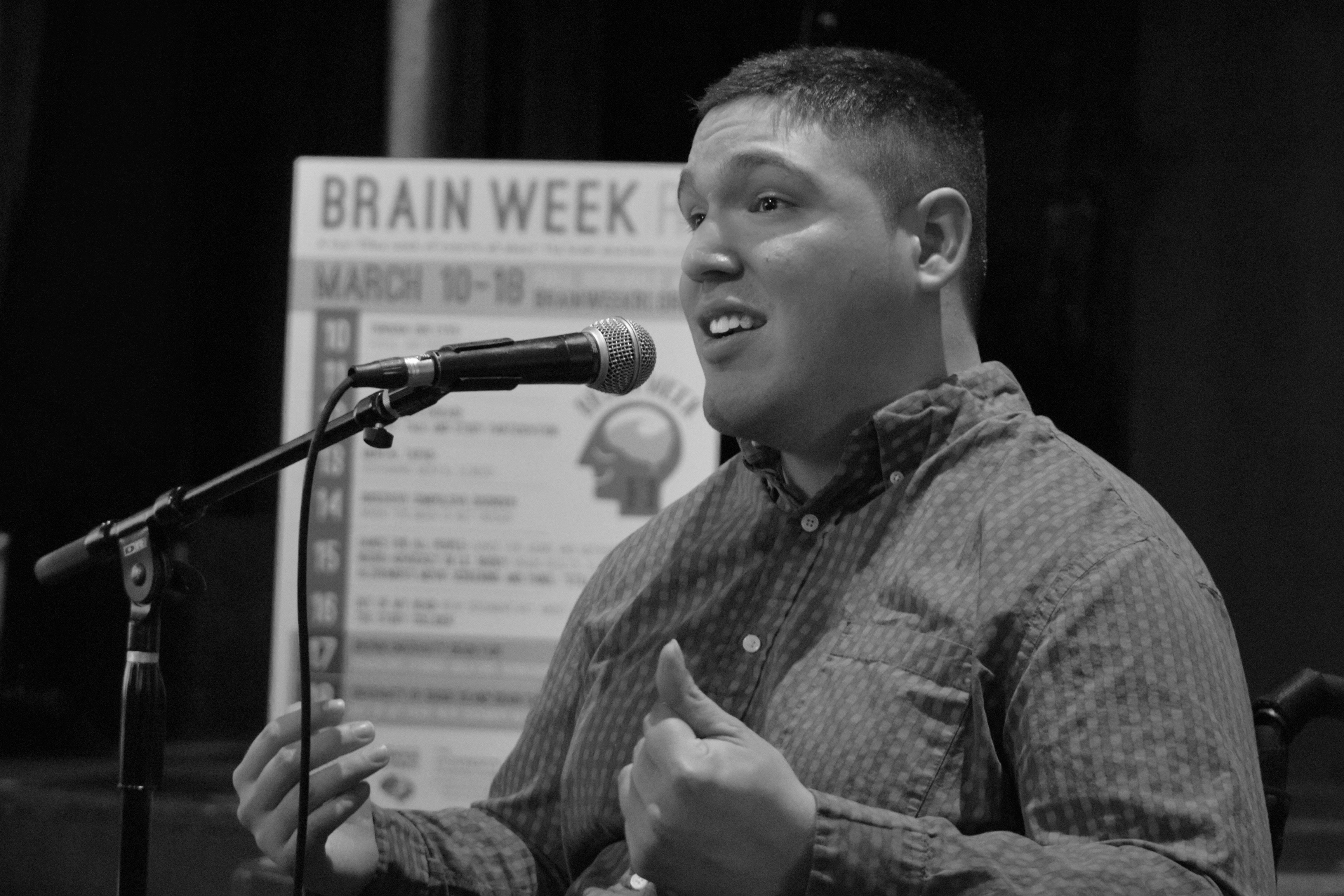 Black and white image of Jose Rosario speaking into microphone