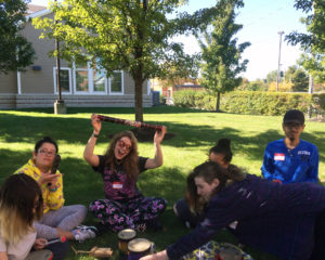 High school students sitting outside, having fun and playing with instruments during an expressive arts workshop